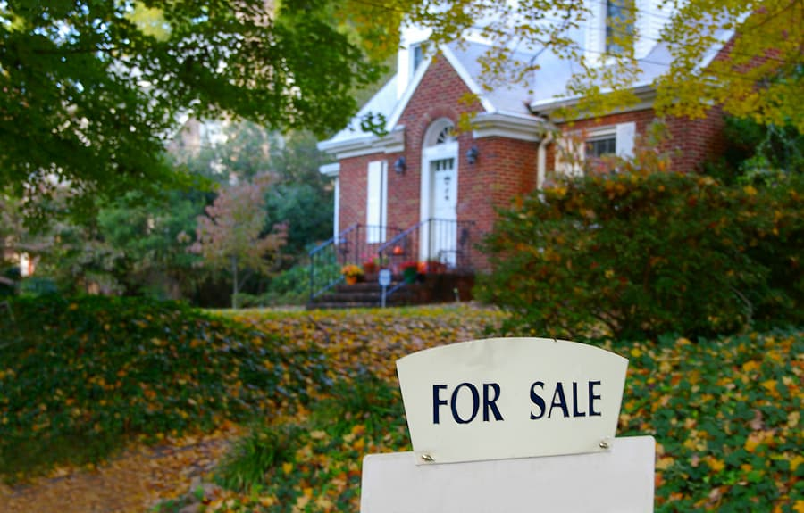 Real estate for sale sign in front of a house